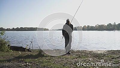 Passage barbu de pêcheur par la caméra avec la canne à pêche L'homme est engagé dans un passe-temps Pêche en eau douce Mouvement  banque de vidéos
