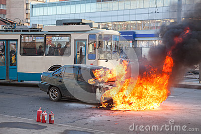 Passenger transport passes near burning car Editorial Photo
