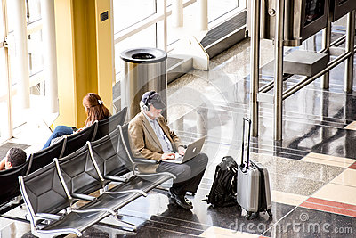 Passengers waiting in front of a bright interior airport window