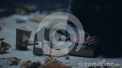 Passer-en donnant de l'argent à un mendiant qui tient une maison de papier et une bible, un abri banque de vidéos