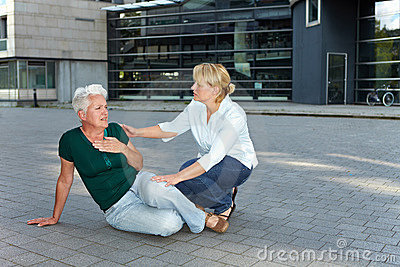 Passerby helping sick senior woman
