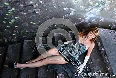 The girl in an evening dress lies on an old ladder
