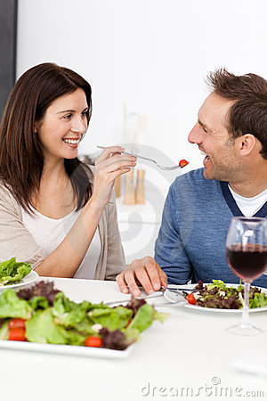 Passionate woman giving a tomato to her husband