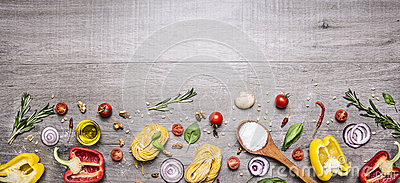 Pasta, tomatoes and ingredients for cooking on rustic background, top view, border. Italian food concept Stock Photo