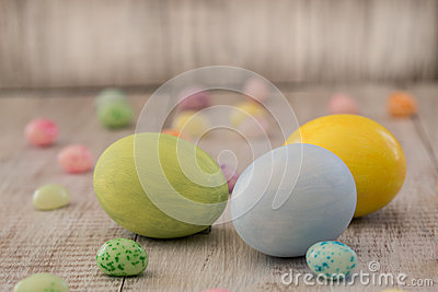 Pastel Painted Easter Eggs and Jelly Beans on Wood Background Stock Photo