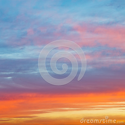 Pastel pink and yellow sunrise clouds in blue sky