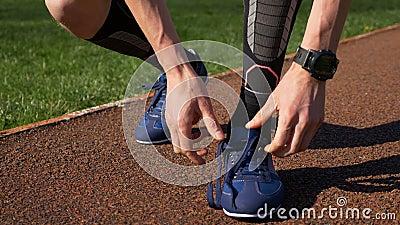 Pasvorm die jogger beide schoenveters binden alvorens praktijk op spoor in werking te stellen stock videobeelden