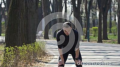 Pasvorm die jogger in een park lopen die een onderbreking nemen en zijn geschiktheidsdrijver slim horloge plaatsen stock videobeelden