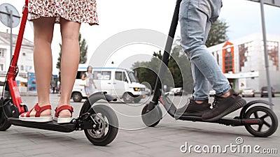 Patas de hombre y mujer montan motocicletas eléctricas de futura tecnología almacen de metraje de vídeo