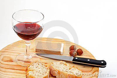 Pate, bread, glass of red wine, hazelnuts and knife on wood plat