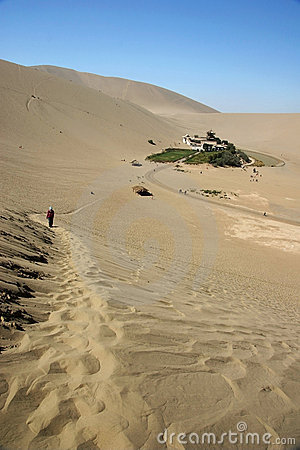 Path in desert with crescent moon lake