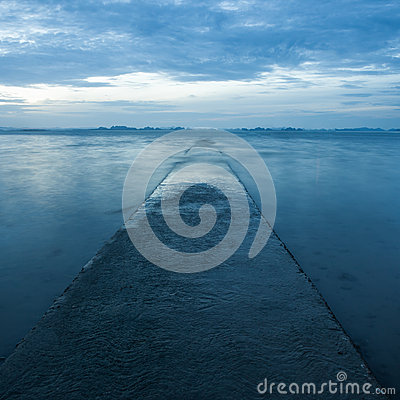 Pathway receding over blue sea