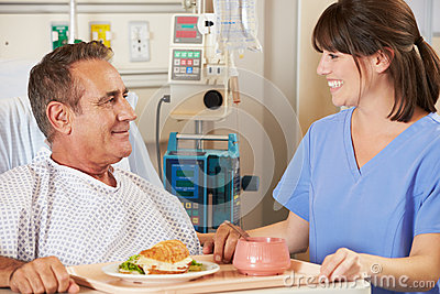 Patient Being Served Meal In Hospital Bed By Nurse