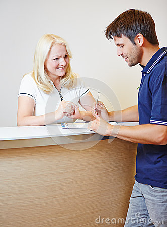 Patient filling out form with doctors assistant