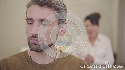 Patient kaukasisch-grauhaarhaariger Mann sitzend und sieht weg, wie seine Mutter ihm die Schuld auf dem Hintergrund gibt Beziehun stock video