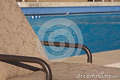 Patio chair next to an aqua blue pool