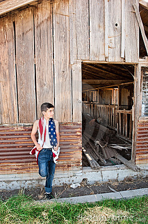 Patriotic boy and old barn