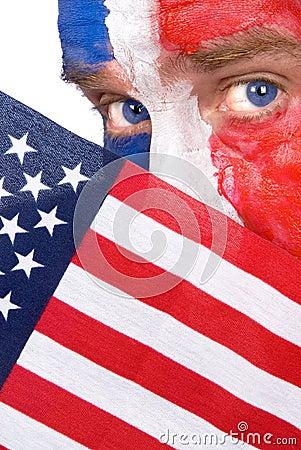 Patriotic man peering over an American flag