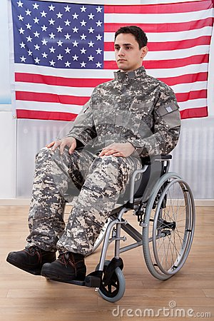 Free Patriotic Soldier Sitting On Wheel Chair Against American Flag Royalty Free Stock Image - 46361216