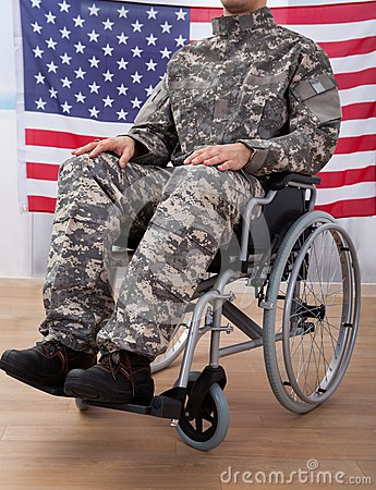 Free Patriotic Soldier Sitting On Wheel Chair Against American Flag Stock Images - 55849574