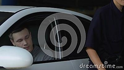 Patrolwoman die parkeerticket voor de chauffeur schrijft, boete wegens overtreding van de verkeersregels stock footage