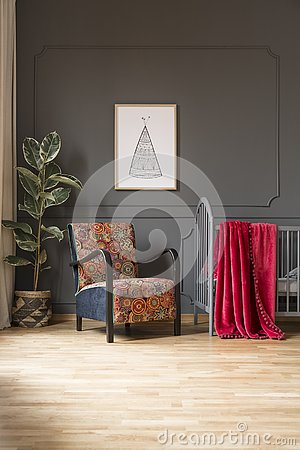 Free Patterned Armchair Next To Bed With Red Blanket In Baby`s Bedroo Royalty Free Stock Images - 126408909