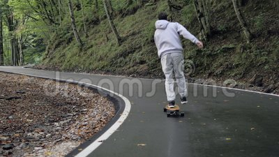 Pattinaggio di cappuccio grigio durante una crociera a bordo lungo una strada tortuosa attraverso la foresta stock footage