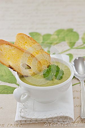 Pea cream soup in white bowl