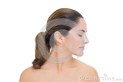 Peaceful bare brunette turning head right with closed eyes