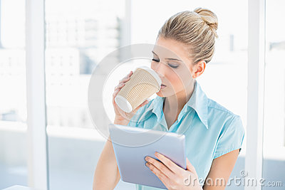 Peaceful classy woman using tablet while drinking coffee