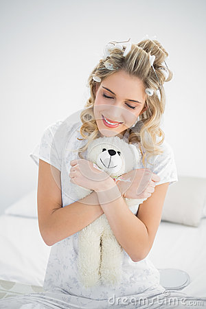 Peaceful pretty blonde wearing hair curlers holding teddy bear