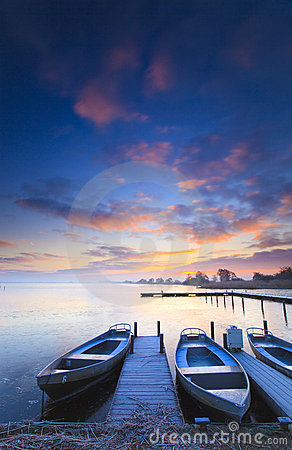 Peaceful sunrise with dramatic sky and boats and a