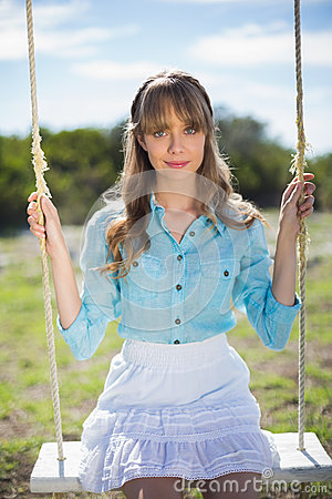 Peaceful young model relaxing while sitting on swing