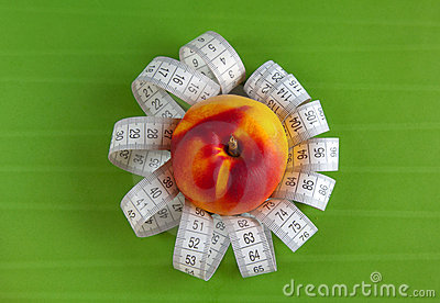 Peach and tape measure on the green background
