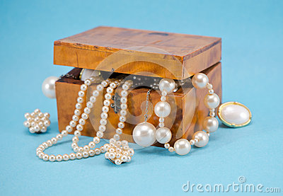 Pearl jewelry defocus in retro wooden box on blue