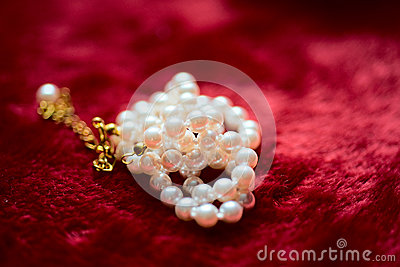 Pearl necklace on plush red material