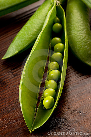 Peas pod open on wood