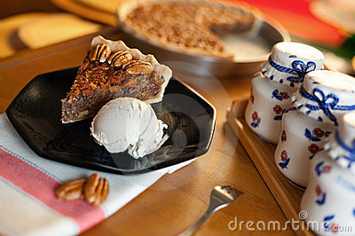 slice of pecan pie served with vanilla ice cream on a black dish ...