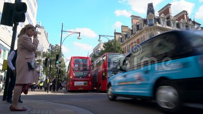 Pedestrian crossing, traffic, taxis and red double decker London buses in Oxford Street, Londen, Engeland stock video