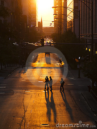 Pedestrians crossing street at sunset