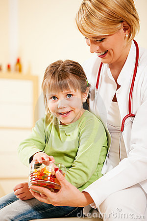 Pediatrician doctor giving candy to little patient Editorial Stock Image