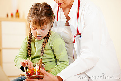 Pediatrician doctor giving candy to little patient Editorial Stock Photo