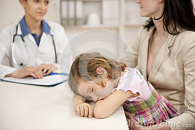 Pediatrician talking to mother and sick child