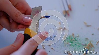 Peintre peintre peintre aiguisant le crayon bleu à l'aide d'un couteau tranchant, les mains closeup banque de vidéos