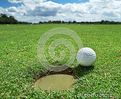 Pelota de golf en el agujero