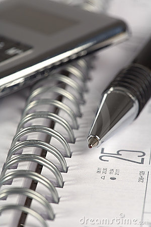 Pen  and calculator on notepad