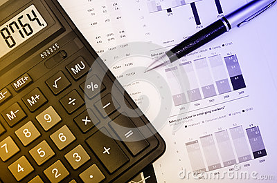Pen and calculator over annual report