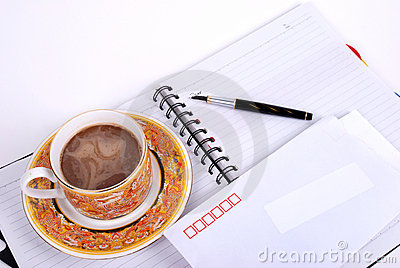 Pen ,coffee and envelop on  notebook