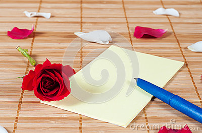 Pen and empty note on a wooden background with a rose and petals