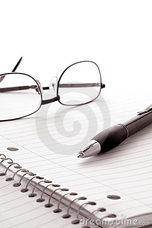 Pen and Glasses on Notebook Blank Paper Sheet